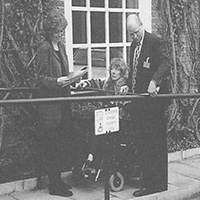 Trainer Ann Sawyers with a lady in a wheelchair and a man, all standing on a ramp
