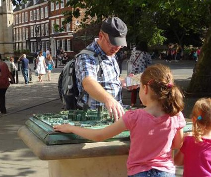 A father and his daughters are pictured engaging with a tactile map of York city centre