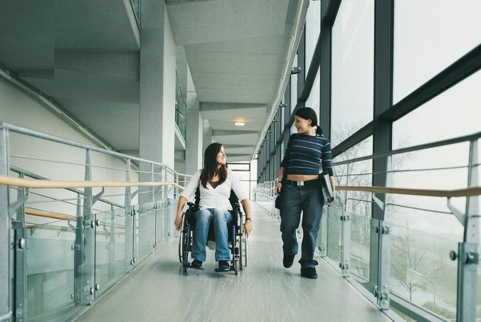 A girl in a wheelchair going down a ramp with another girl walking beside her.
